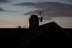 屋顶和烟囱在晚上 免版税库存照片