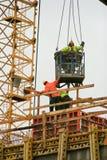 屋顶模铸混凝土的建筑工人从起重机降下了 免版税库存图片