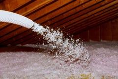 屋顶的喷洒的吹的玻璃纤维绝缘材料-使用复数组分枪的技术员喷洒的泡沫绝缘材料 图库摄影