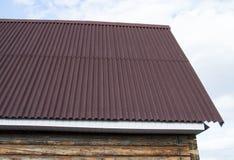 屋顶的现代建筑有支持对一个木房子的红色金属的在庭院里 免版税库存图片