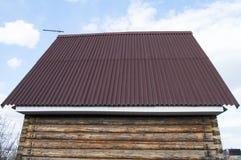 屋顶的现代建筑有支持对一个木房子的红色金属的在庭院里 免版税库存照片