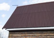 屋顶的现代建筑有支持对一个木房子的红色金属的在庭院里 图库摄影