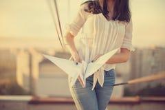 屋顶的美丽的女孩有origami纸起重机的在手上 免版税图库摄影