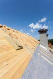 屋顶绝缘材料 新的木房子建设中有反对蓝天的烟囱的 图库摄影