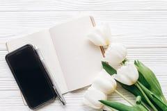 给屏幕和笔记本笔和时髦的郁金香打电话在白色木 免版税图库摄影