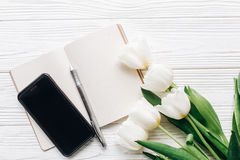 给屏幕和笔记本笔和时髦的郁金香打电话在白色木 图库摄影