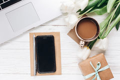 给屏幕和膝上型计算机打电话用早晨咖啡和郁金香在白色 免版税库存照片