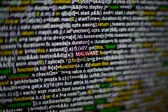 屏幕和被突出的MALWARE题字宏观照片有节目原始代码的在中部 在的剧本 图库摄影