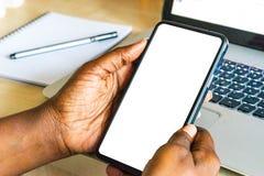 屏幕手机,在非洲妇女的手上 在绿色室外背景的黑女性举行的智能手机与空白的拷贝s 库存照片