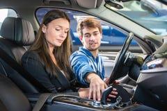 展示中间人汽车的技工给一名潜在的顾客 免版税库存照片