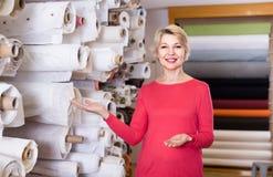 展示分类的女性售货员在纺织品商店 免版税库存图片