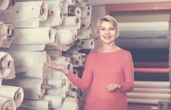 展示分类的女性售货员在纺织品商店 免版税库存照片
