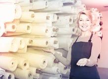 展示分类的女性售货员在纺织品商店 图库摄影