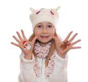 展示在她的手上的愉快的女孩被绘的圣诞节标志 圣诞老人,驯鹿 免版税库存照片