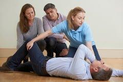 展示在急救的妇女补救位置训练Clas 库存照片