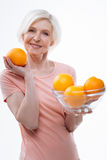 展示大桔子的正面高兴年迈的金发碧眼的女人 免版税库存照片