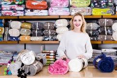 展示家庭纺织品的分类的女性售货员 库存图片