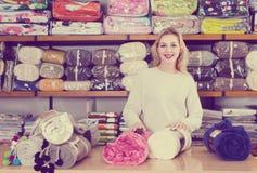展示家庭纺织品的分类的女性售货员 免版税库存照片