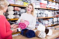 展示床罩的女性卖主给纺织品的资深买家 免版税图库摄影
