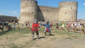 展示战斗的技能的装甲的未认出的人在比赛重建时在城堡附近 免版税库存照片