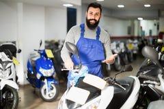 展示摩托车和滑行车的工作者 免版税库存照片