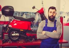 展示摩托车和滑行车的男性工作者 免版税库存照片