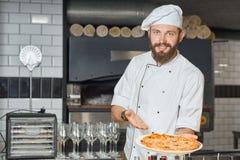 展示新鲜的被烘烤的可口薄饼的愉快的pizzaiolo 免版税库存照片