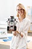 展示未来派机器人的成功的工程师在实验室里 免版税库存照片