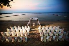 展示椅子为婚姻或在海滩的另一顿承办宴席的事件晚餐设置了 免版税库存图片