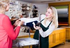 展示织品的殷勤女性卖主给资深买家  图库摄影