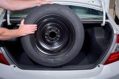 展示从树干的备用轮胎撤除 图库摄影