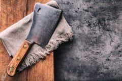 屠户 葡萄酒有布料毛巾的屠宰肉砍肉刀在黑暗的具体或木厨房板 免版税库存图片