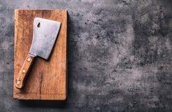屠户 葡萄酒有布料毛巾的屠宰肉砍肉刀在黑暗的具体或木厨房板 图库摄影