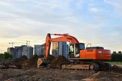 履带牵引装置挖掘机在塔吊和多层的居民住房背景的工地工作  免版税库存照片