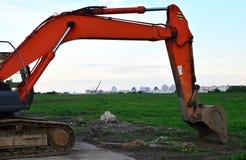 履带牵引装置挖掘机在天空蔚蓝背景的工地工作 特别重型建筑设备 免版税库存图片