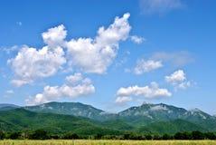 山、云彩和草甸 免版税库存图片