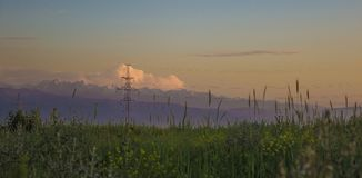 山、日落天空、夏天领域和高压耸立, Kaza 库存图片