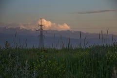 山、日落天空、夏天领域和高压耸立, Kaza 图库摄影