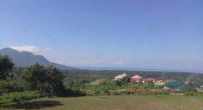 山、海和云彩在村庄 免版税库存图片