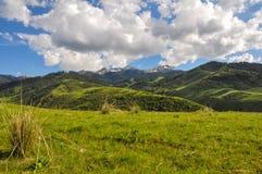 山、草、天空和云彩 库存图片