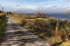 山、路、湖和植被在西部方式足迹在港湾Corrib 免版税库存照片