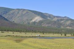 山、领域和一个小的湖美好的风景  库存照片