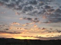 山、领域和多云天空在春天 库存图片