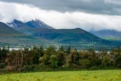 山、领域和湖在多云天在基拉尼爱尔兰 免版税库存照片