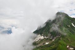 山上面在与草和雪的夏天以天空和云彩为背景 库存照片