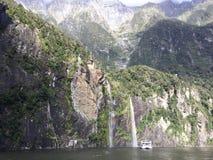 从山上面的瀑布与彩虹和风景巡航渡轮,新西兰 库存照片
