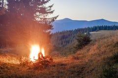山与篝火的晚上与在前面的闪闪发光 图库摄影
