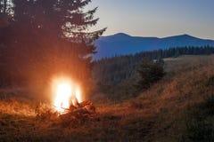 山与篝火的晚上与在前面的闪闪发光 库存照片