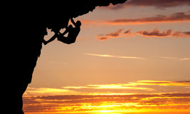 登山人剪影岩石面孔的 免版税库存图片
