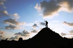 登山人在小山顶部的成功剪影 免版税图库摄影